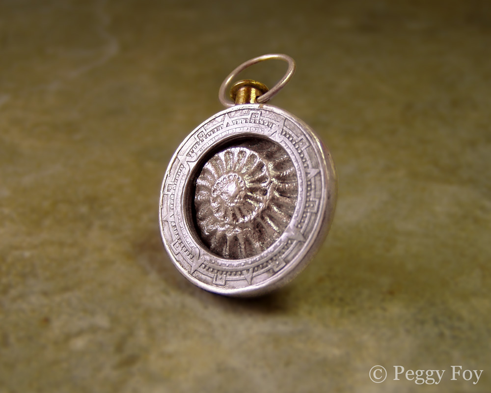 An art jewelry pendant by Peggy Foy featuring a sterling silver ammonite surrounded by a coin fragment depicting part of the Mayan calendar.