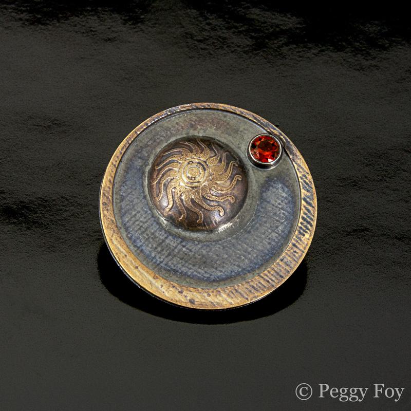 """Orbit: Sun and Mars; (brooch)  sterling, brass, garnet, nickel pinstem; 1"""" diameter; 2013."""