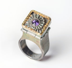 A tall ring with a hinged compartment, with a spiral fossil motif, a purple gem, and a gold border.